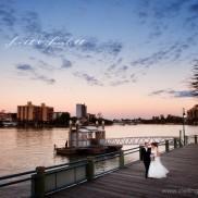 landing at dockside wedding bride and groom on the boardwalk at sunset